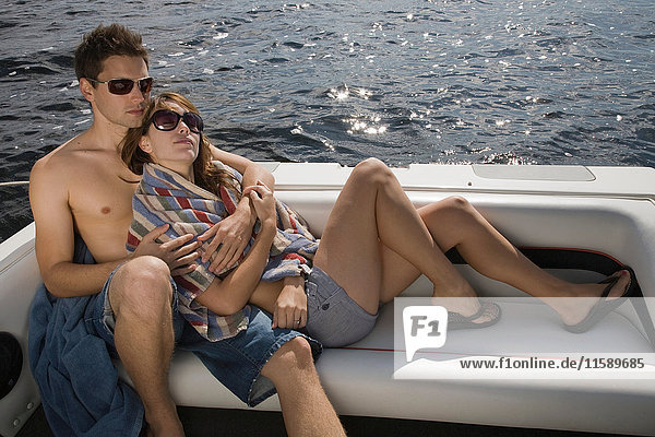 Couple relaxing in speedboat on lake