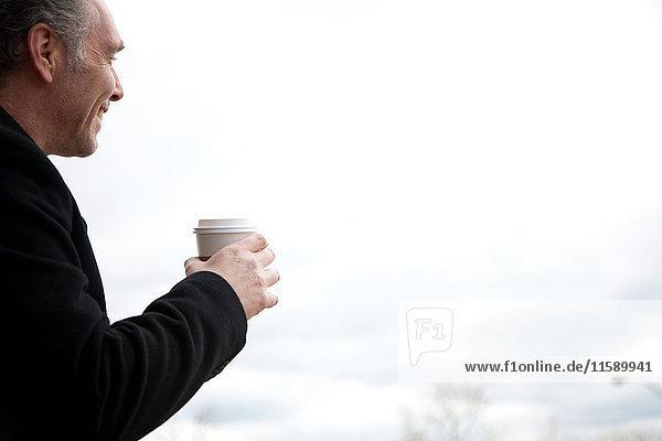 Reifer Mann trinkt Kaffee im Freien