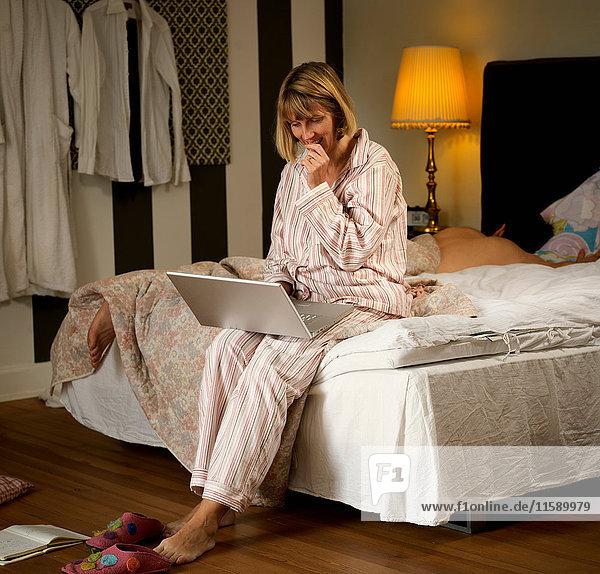Reife Frau sitzt im Pyjama auf dem Bett und benutzt Laptop