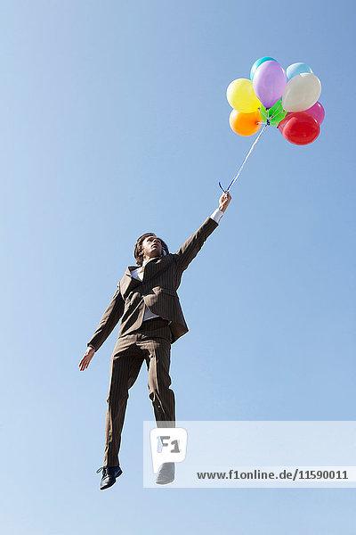 Mit Luftballons schwebender Geschäftsmann