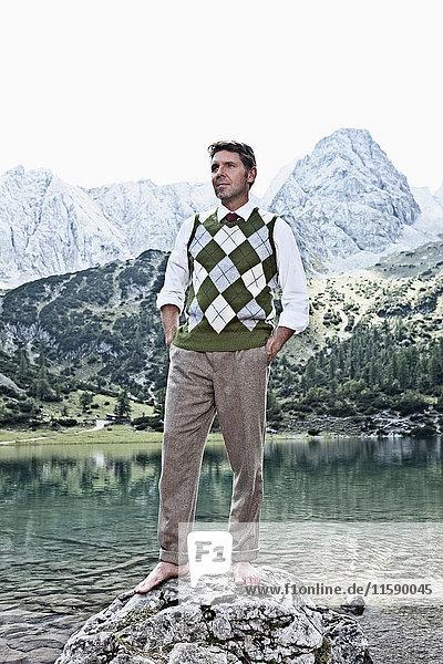 Barfüssiger Mann am See stehend