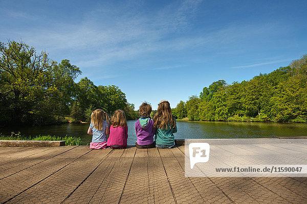 Kinder sitzen auf einem Holzdock im See Kinder sitzen auf einem Holzdock im See