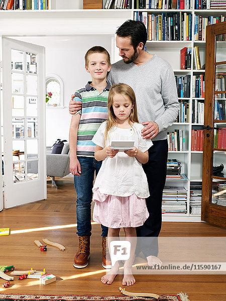 Vater und Familie stehen zusammen im Wohnzimmer  Porträt