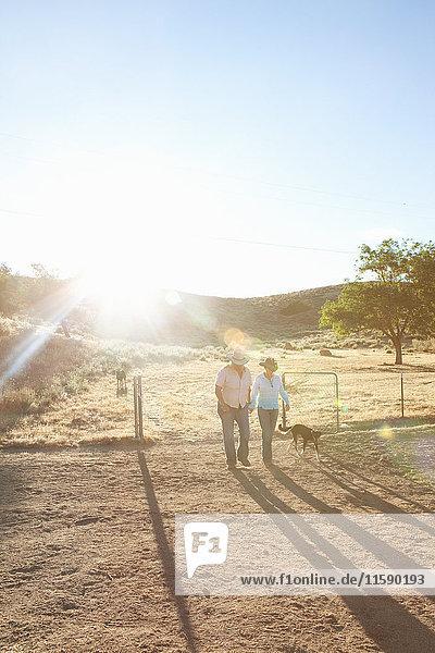 Ein reifes lesbisches Paar geht bei Sonnenuntergang durch die Ranch
