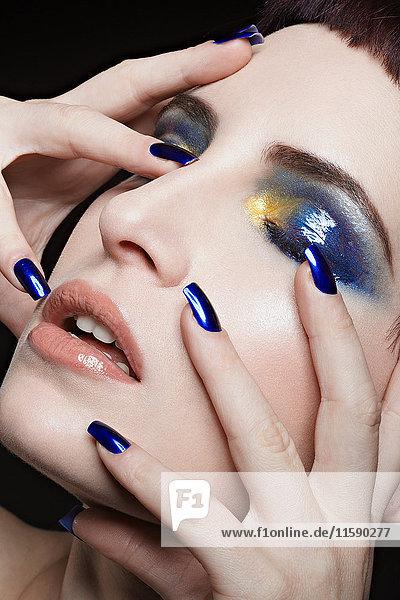 Junge Frau mit blauem Nagellack und Lidschatten im Gesicht