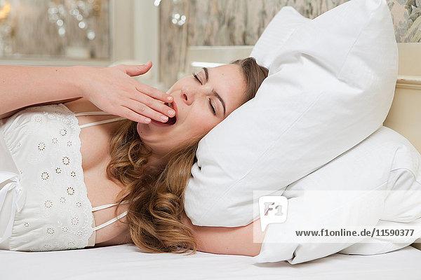 Frau im Bett gähnend