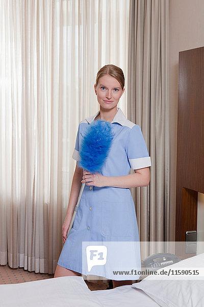 Zimmermädchen mit Staubwedel im Hotelzimmer