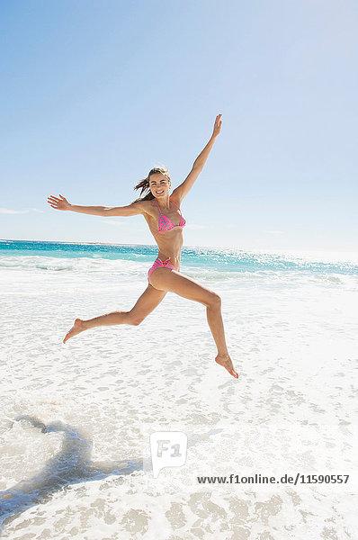Ein Mädchen springt auf den Strand