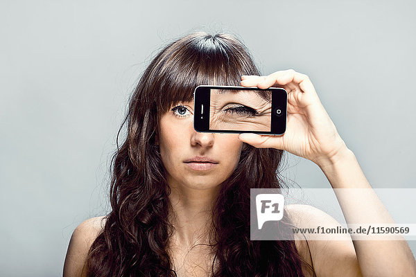 Frau mit Handy-Bild des Auges