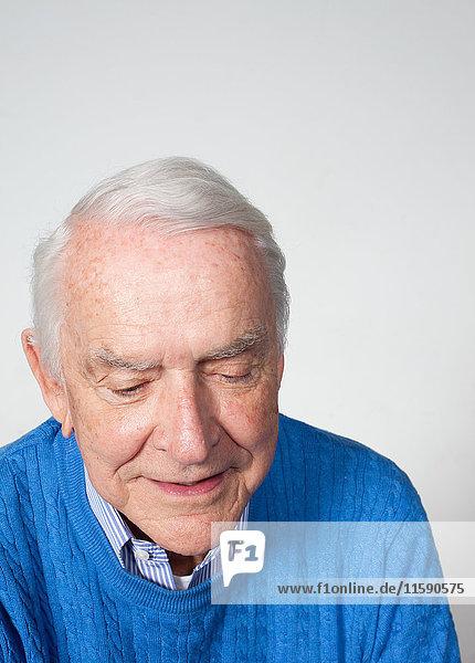 Älterer Mann schaut nach unten  Studioaufnahme