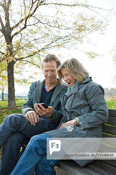 Mutter und erwachsener Sohn auf Parkbank mit Blick auf Smartphone