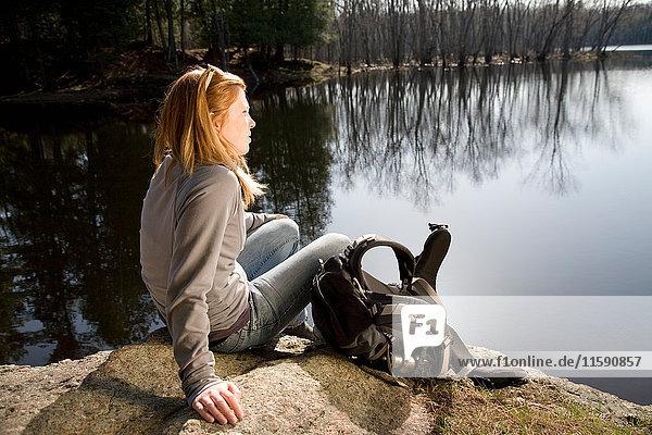Woman resting beside lake