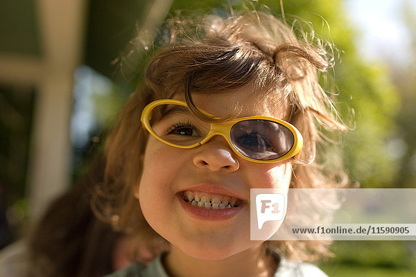 Young girl wearing broken sunglasses