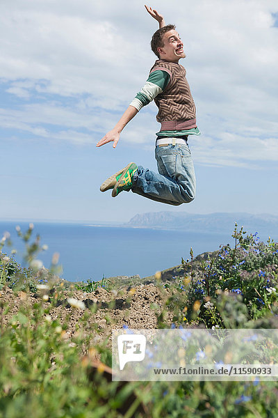 junger Mann springt in die Luft