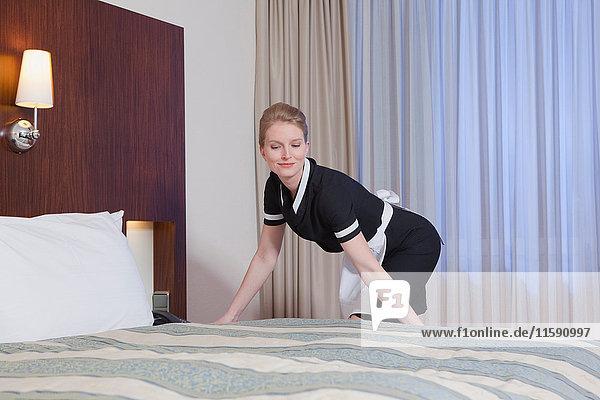 Zimmermädchen beim Bettenmachen  lachend