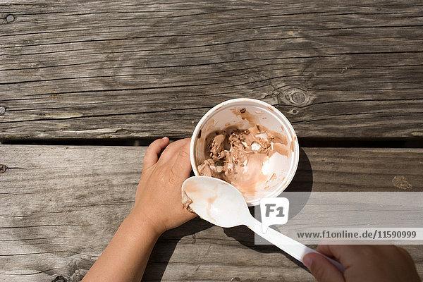 Junges Mädchen isst eine Schüssel Eiscreme mit Löffel