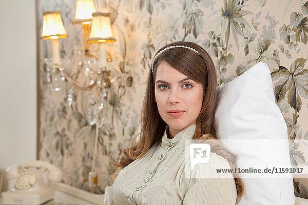junge Frau im Bett sitzend