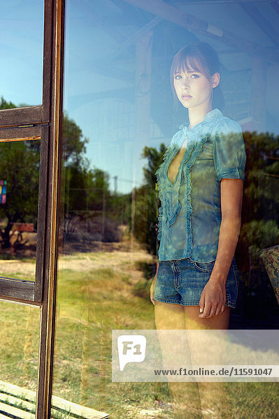 Teenage girl standing in window