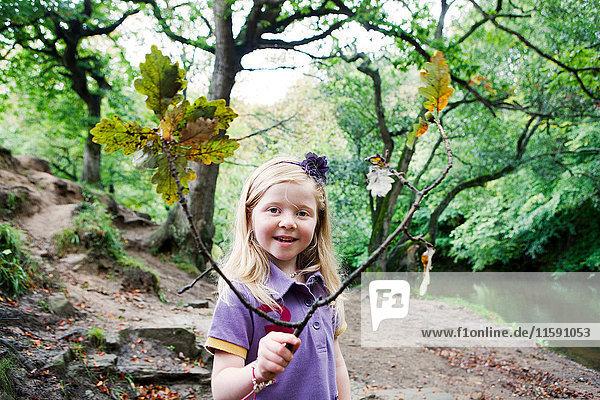 Mädchen hält einen Eichenast in einem Waldgebiet