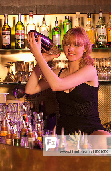 weiblicher Baarkeeper schüttelt Cocktail