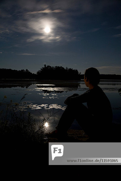 Woman watching moon over lake