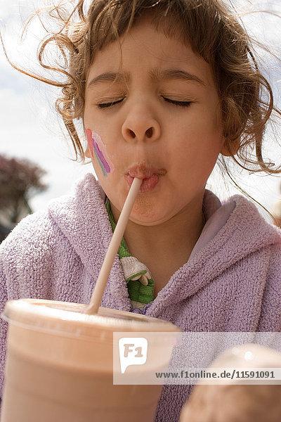 Young girl drinking milkshake