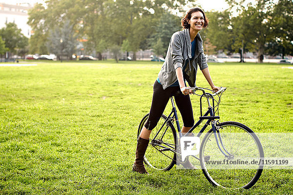 Young woman on bicycle in park