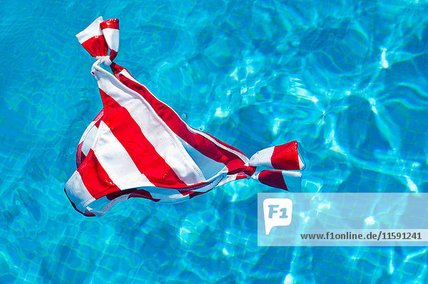 Red and white striped bikini bottoms floating on water surface