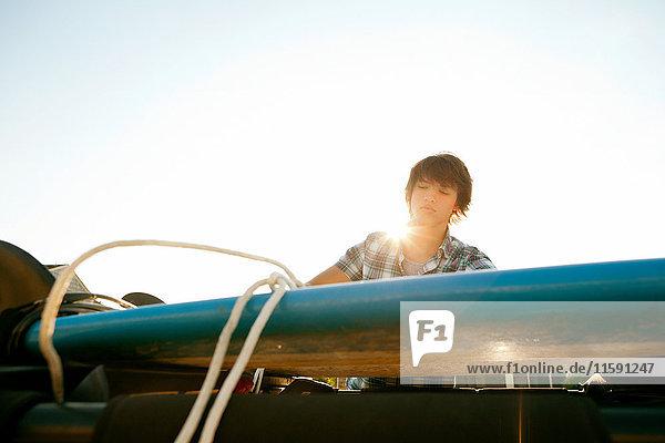 Teenager bindet sein Brett vom Dach des Jeeps ab