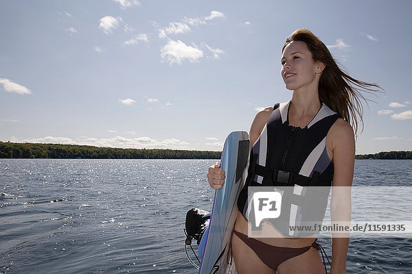 Woman holding wakeboard by lake