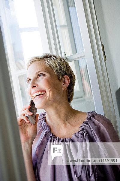 Frau am Fenster mit Mobiltelefon