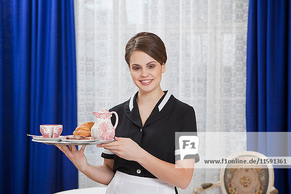 Zimmermädchen mit Tablett  lachend
