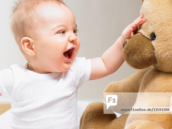 Baby spielt mit einem Teddybär