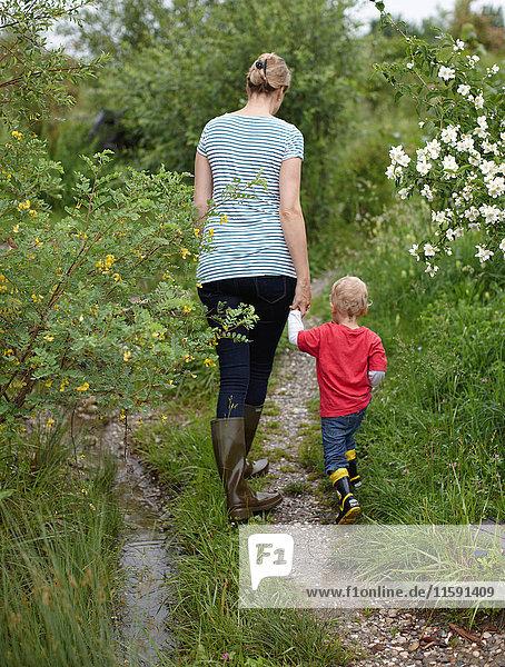 Mutter und Sohn gehen auf einem Feldweg