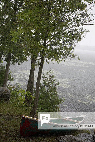 Canoe in rain by lake