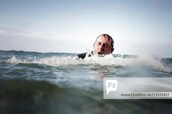 Ein Geschäftsmann kommt aus dem Meer