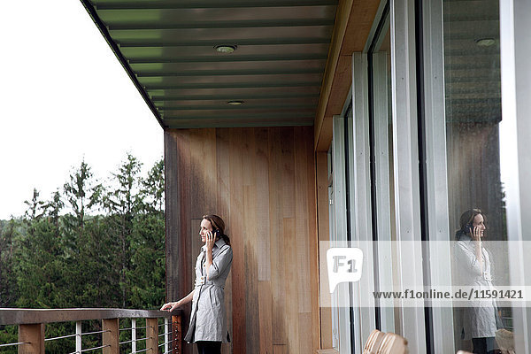 Frau mit Regenmantel am Mobiltelefon