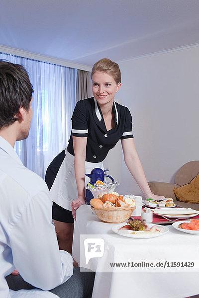 Zimmermädchen  das dem Geschäftsmann das Frühstück serviert