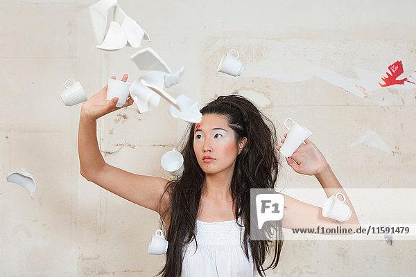 Frau wirft zerbrochene Tassen