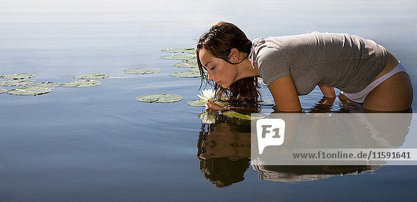 Woman smelling flower in lake