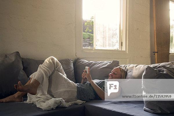 Lächelnde Frau auf der Couch liegend mit dem Handy