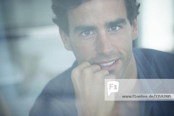 Porträt des lächelnden jungen Mannes hinter der Fensterscheibe