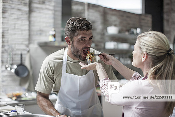 Couple cooking together and tasting food in kitchen