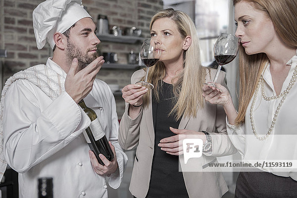 Chef with two women in kitchen tasting wine