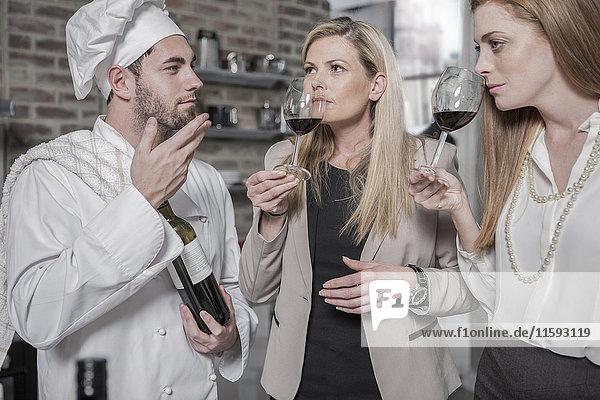 Chefkoch mit zwei Frauen in der Küche bei einer Weinprobe