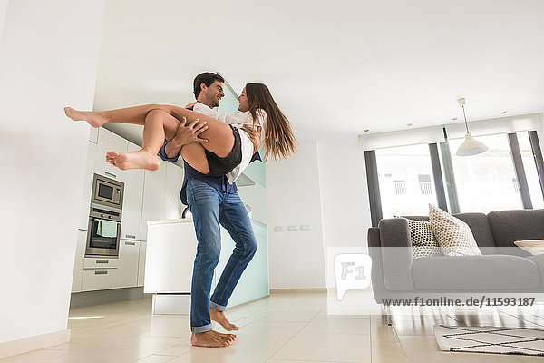 Playful young man carrying girlfriend at home