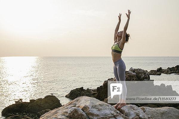 Frau beim Yoga am Strand