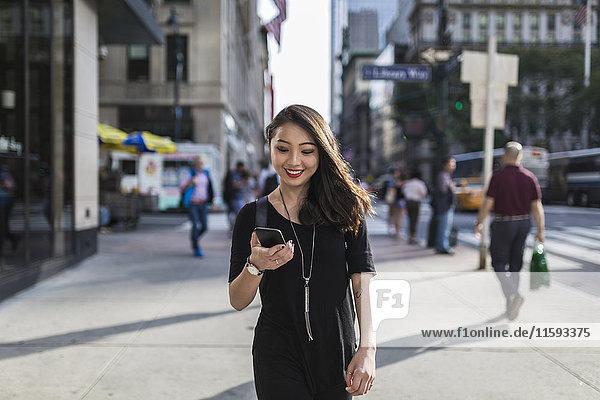 USA  New York City  Manhattan  Porträt einer lächelnden jungen Frau in Schwarz mit Blick auf das Handy
