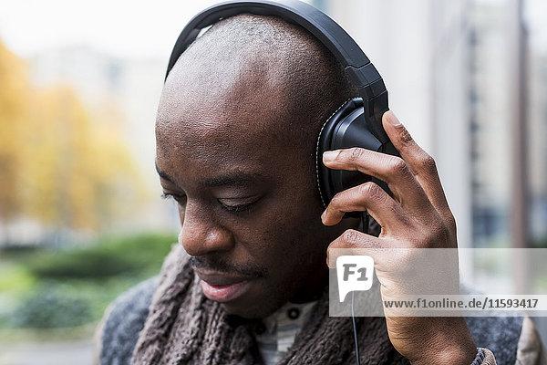 Kahler Mann hört Musik mit Kopfhörern