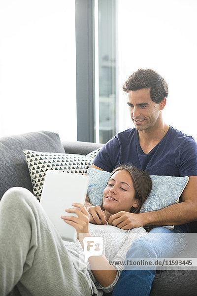 Junges Paar mit Tablette zum Entspannen zu Hause